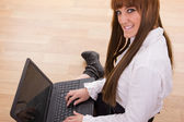Smiling business woman typing on laptop keyboard on the floor — Stock Photo