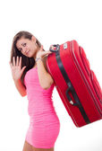 Beautiful young woman with travel suitcase saying goodbuy — Stock Photo