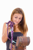 Undecided girl takes out jewelery from jewelry box — Stock Photo
