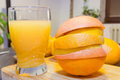 Fresh orange juice and slices on wooden board — Stock Photo