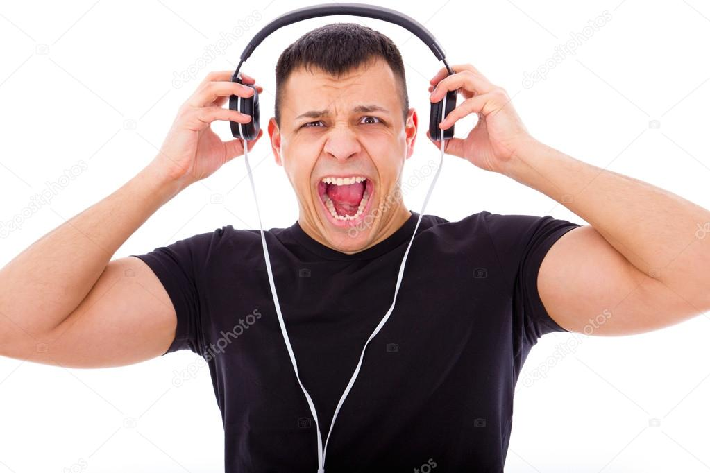 Angry man yelling listening to loud music with headphones ...