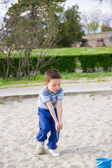 Little boy with sand in hands rush to the bucket for sand — Foto Stock