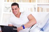 šťastný mladý muž ležel na pohovce, pracují na přenosném počítači — Stock fotografie
