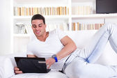 Man relaxing on sofa with laptop computer — Stok fotoğraf