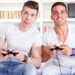Two male friends playing video game with controllers — Stock Photo