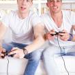 Two modern guys playing computer game holding controllers — Stock Photo #43790235