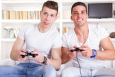 Two male friends playing video game with controllers — 图库照片