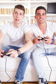 Two modern guys playing computer game holding controllers — Stock Photo