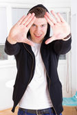 Cool young guy in hooded jacket framing his face with hands — Stock Photo