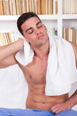 Relaxed man drying hair with white towel — Stock Photo