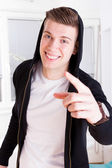 Young guy with great smile in active sportswear hood pointing — Stock Photo