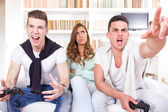 Bored women between two casual passionate men playing video game — Stock Photo