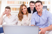 Casual group of friends sitting on couch looking at laptop — Stock Photo