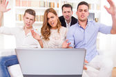 Hocked casual group of friends sitting on couch looking at lapto — Stock Photo