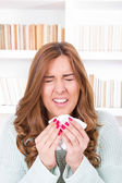 Sick woman sniffles with virus feeling ill sneezing into tissue — Stock Photo