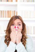 Sick woman with cold and virus sneezing into tissue — Stock Photo