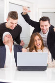 Excited happy group of friends winning online using laptop — Stock Photo