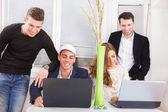 Équipe sympathique regardant sourire d'ordinateur portable — Photo