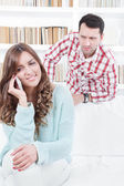 Jealous worried man peering over the shoulder of his girlfriend — Stock Photo