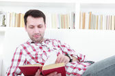 Young casual man reading a book relaxing on sofa — Stock Photo
