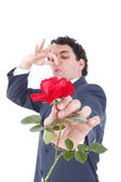 Man in suit throws a rose and gives it to the camera while the o — Stock Photo
