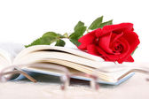 Book and red rose on pages of book on white background with glas — Stock Photo