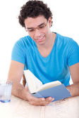 Man in blue t-shirt sitting at table and reading book — Foto Stock