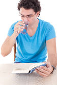 Man in blue t-shirt with glasses sitting at table and reading bo — Foto de Stock