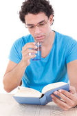 Man reading book while drinking healthy water from a glass — Foto de Stock