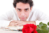 Man relaxing with flower and good book with glasses aside — Foto de Stock