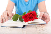 Man with his hands holding open book while rose and glasses are  — Stock Photo