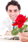 Romantic man holding rose with book and glasses on table — Photo