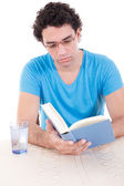 Serious man in blue t-shirt sitting at table and reading book — Foto Stock