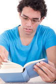 Thoughtful man in blue t-shirt with glasses sitting at table and — Foto de Stock