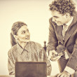 Boss and smiling secretary working together on laptop — Stock Photo