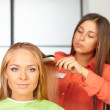 Hair salon. Womens haircut. Use of straightener. — Stock Photo