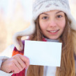 Young beautiful girl with blank banner. Winter. — Stock Photo #33749365