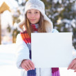 Young beautiful girl with blank banner. Winter. — Stock Photo