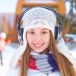 Outdoors on a winter day. Girl listen music. — Stock Photo #34448375