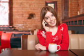 Girl in cafe. On the phone. — Stock Photo