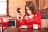 Beautiful girl picking up sms on mobile phone in cafe. — Stock Photo