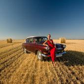 Meisje leunend op retro auto met strobalen achtergrond. — Stockfoto