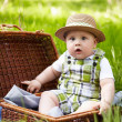 Little boy in the garden. Playing with picnic basket. — Stock Photo