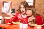Beautiful girls eat sushi rolls at sushi bar. — Foto Stock