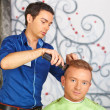 Stock Photo: Hair salon. Hairdresser does haircut for man.