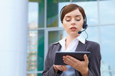 Businesswoman with headset and tablet pc. — Stock Photo