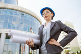 Architect holds construction plans. — Stock Photo