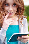 Young woman reads with e-books reader. — Stock Photo