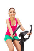 Young woman uses stationary bicycle trainer. — Stock Photo