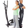 Young man and woman with elliptical cross trainer. — Stock Photo